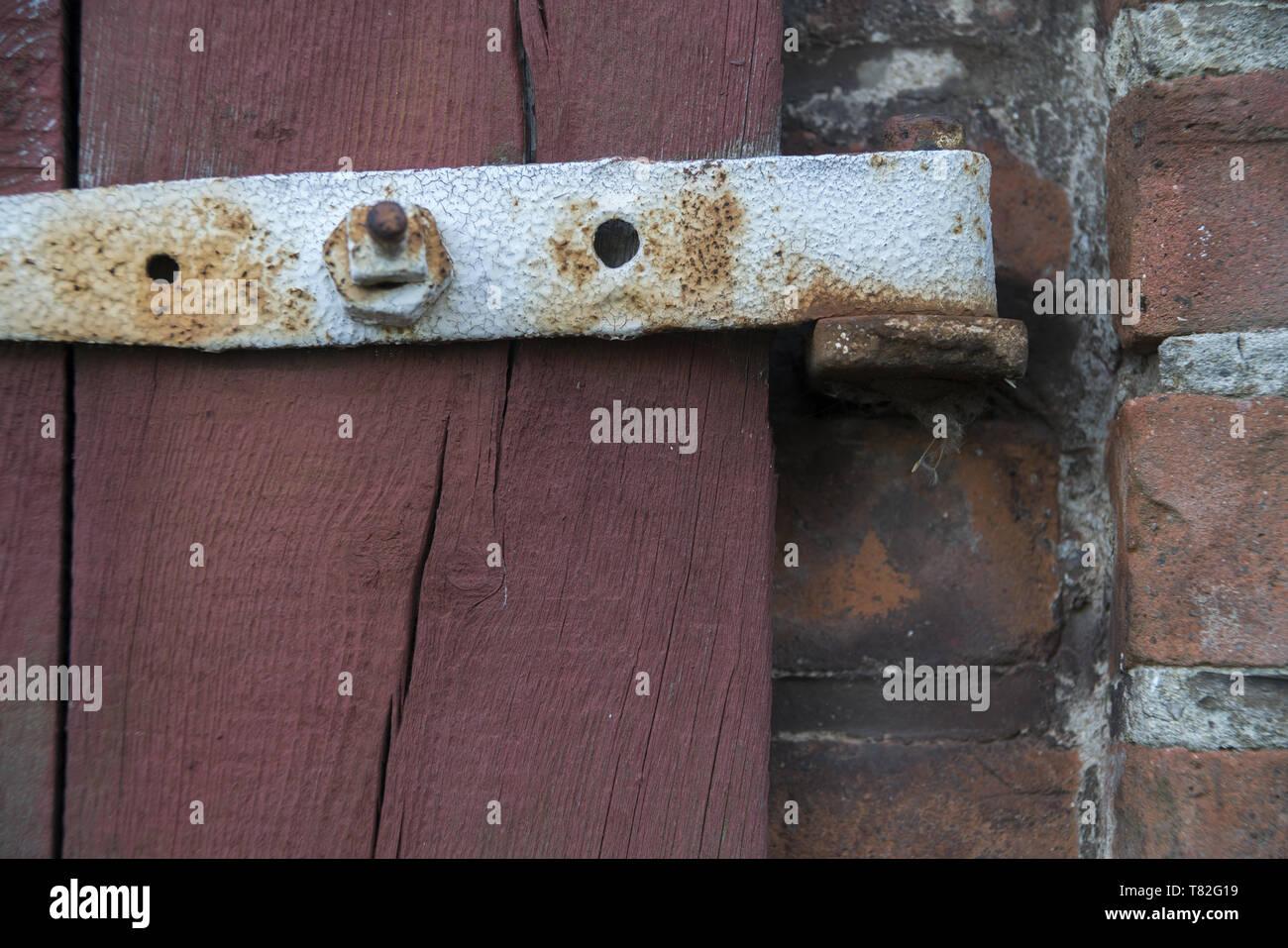 A fragment of an old wooden door with a rusty hinge. Ein Fragment einer alten Holztür mit einem rostigen Scharnier. Fragment starych drzwi z zawiasą. Stock Photo
