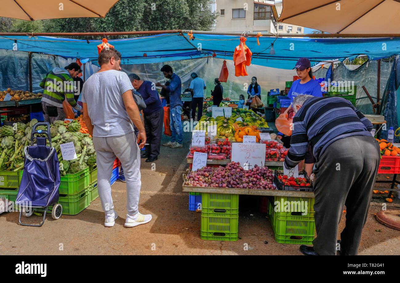 Limassol, Cyprus - March 23, 2019:  Outdoor fruit and vegetable farmer's market in Limassol, held on a Saturday.  Shows shoppers chosing their produce Stock Photo