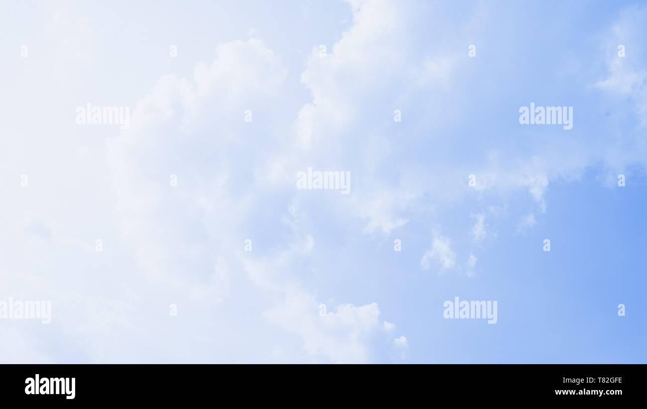 Scenic soft light sky. Beautiful white soft fluffy clouds on a blue sky background. 16:9 panoramic format - Stock Image