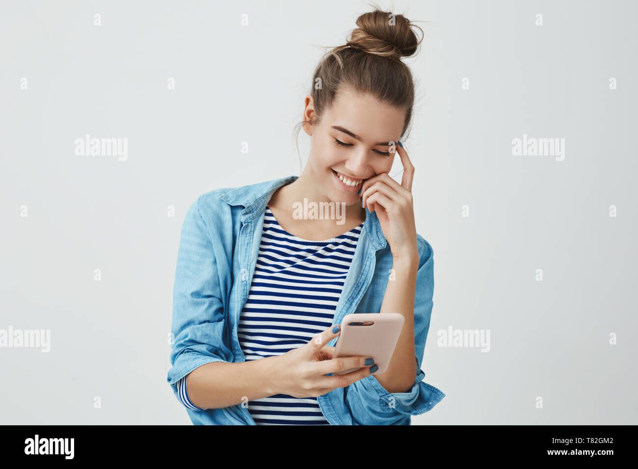 Carefree attractive young european romantic girlfriend 25s, standing cozy clothes hairbun reading touching funny message smiling laughing happily - Stock Image