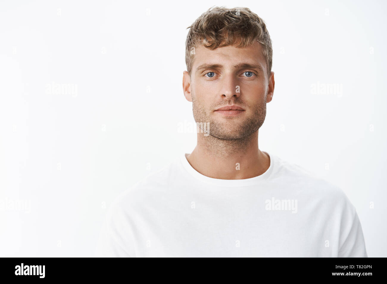 Waist-up shot of handsome calm blond blue-eyed guy with bristle in white t-shirt looking at camera with relaxed carefree facial expression posing over - Stock Image