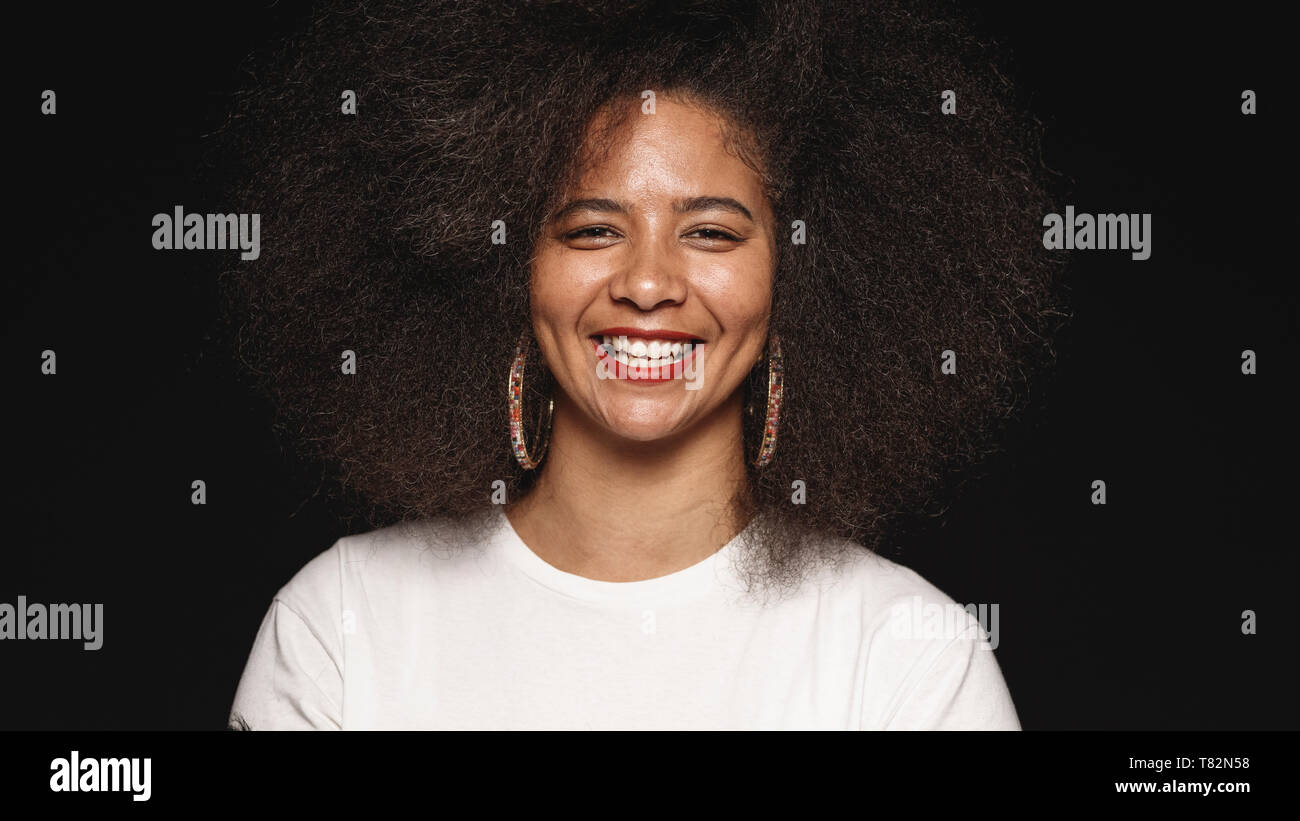 Happy african american female in afro hairstyle isolated on black background. Close up of smiling woman looking at camera. - Stock Image