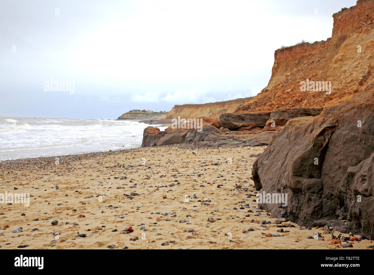A view of the beach and cliffs showing the effects of coast erosion on the Norfolk coast at Happisburgh, Norfolk, England, United Kingdom, Europe. - Stock Image