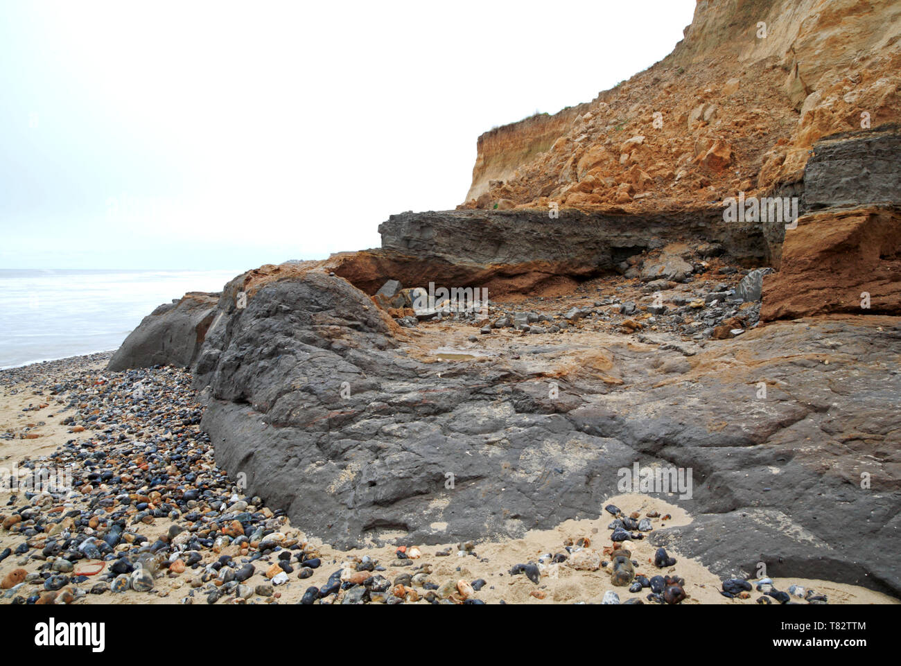Coast erosion with soft cliffs of glacial sands and gravels and a clay base at Happisburgh, Norfolk, England, United Kingdom, Europe. - Stock Image
