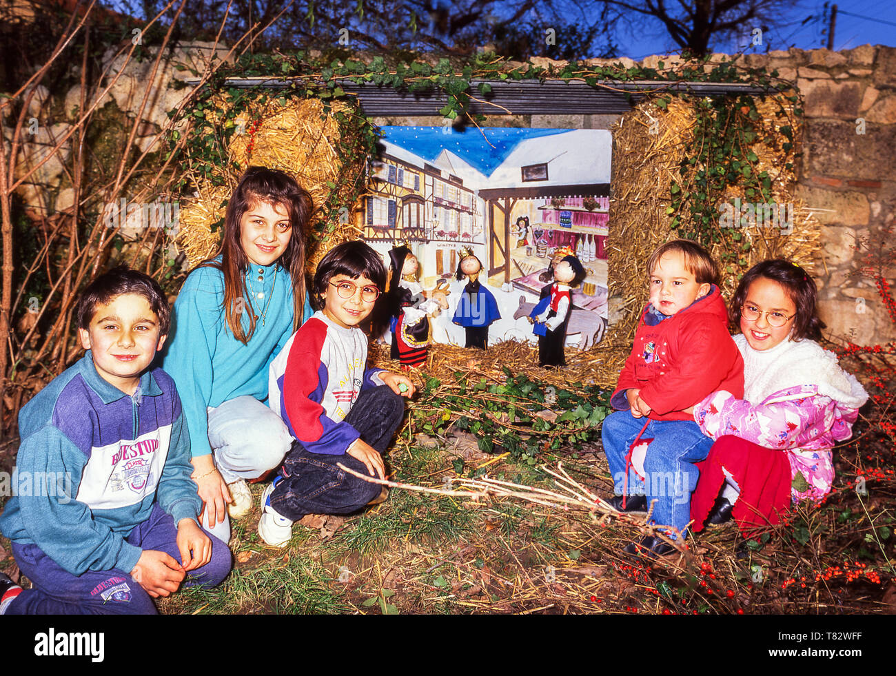 French children with their Christmas tableau they helped to build in their village main square.Dept.Tarn et Garonne. - Stock Image