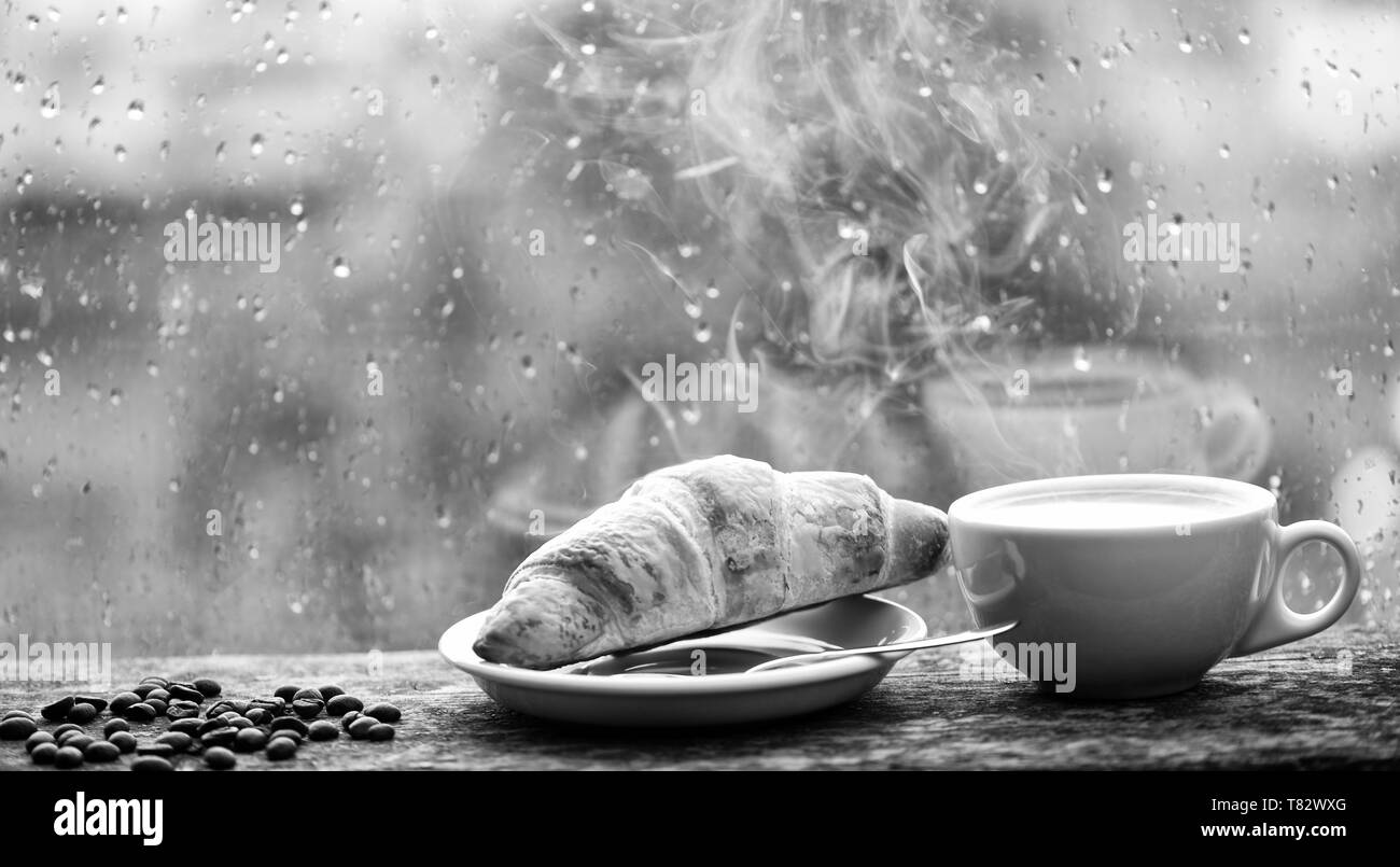 Coffee drink with croissant dessert. Enjoying coffee on rainy day. Coffee time on rainy day. Fresh brewed coffee in white cup or mug on windowsill. Wet glass window and cup of hot caffeine beverage. - Stock Image
