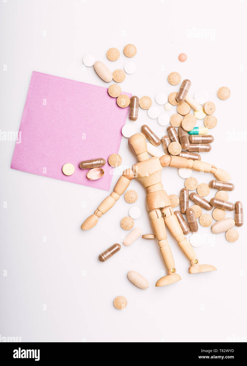 Health and treatment. Health care and problems. Immunity and medicine vitamins. Overdose and death. Medicine prescription. Wooden human dummy lay on pile of pills and tablets. Take medicine concept. Stock Photo