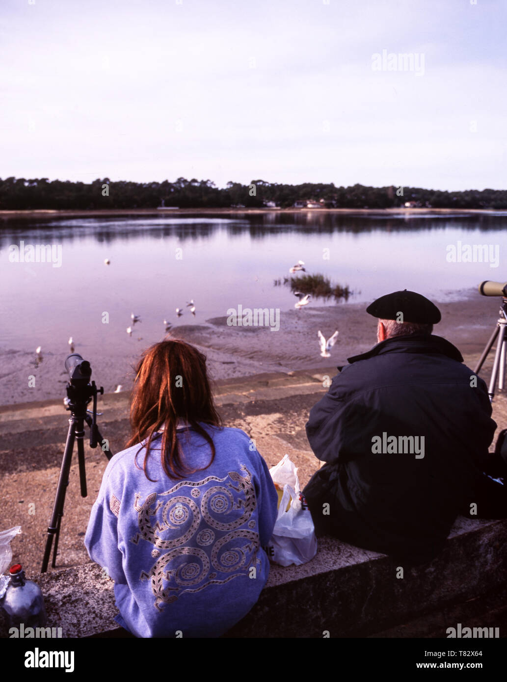 Two French birdwatchers viewing over Hossegor Lake.The lake is on the Atlantic coast of France near the town of Capbreton. Dept.Pyrenees-Atlantiques. - Stock Image
