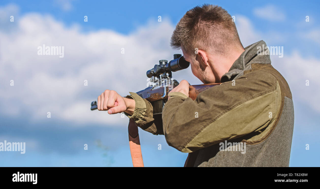 Bearded hunter spend leisure hunting. Hunting optics equipment for professionals. Brutal masculine hobby. Man aiming target nature background. Aiming skills. Hunter hold rifle aiming. On my target. - Stock Image