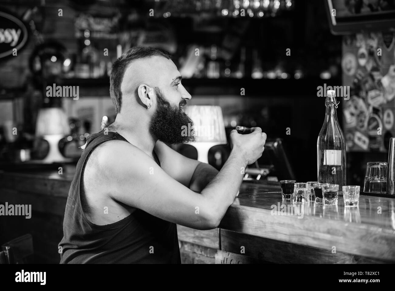 Hipster brutal man drinking alcohol ordering more drinks at bar counter. Guy spend leisure in bar with alcohol. Man drunk sit alone in pub. Alcoholism and depression. Alcohol addicted concept. - Stock Image