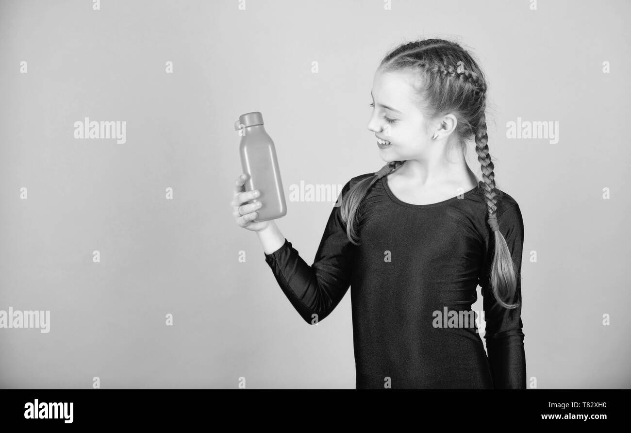 Kid cute girl gymnast sports leotard hold bottle for drink. Water balance and hard gym training. Drink more water. Keep water bottle with you. Quench thirst. Child feel thirst after sport training. - Stock Image