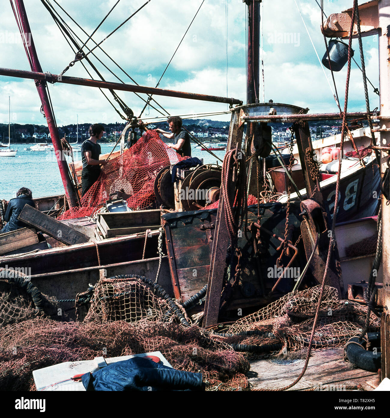 Fishing boat in harbour. Men repairing the net .Conway in North Wales.Great Britain. - Stock Image