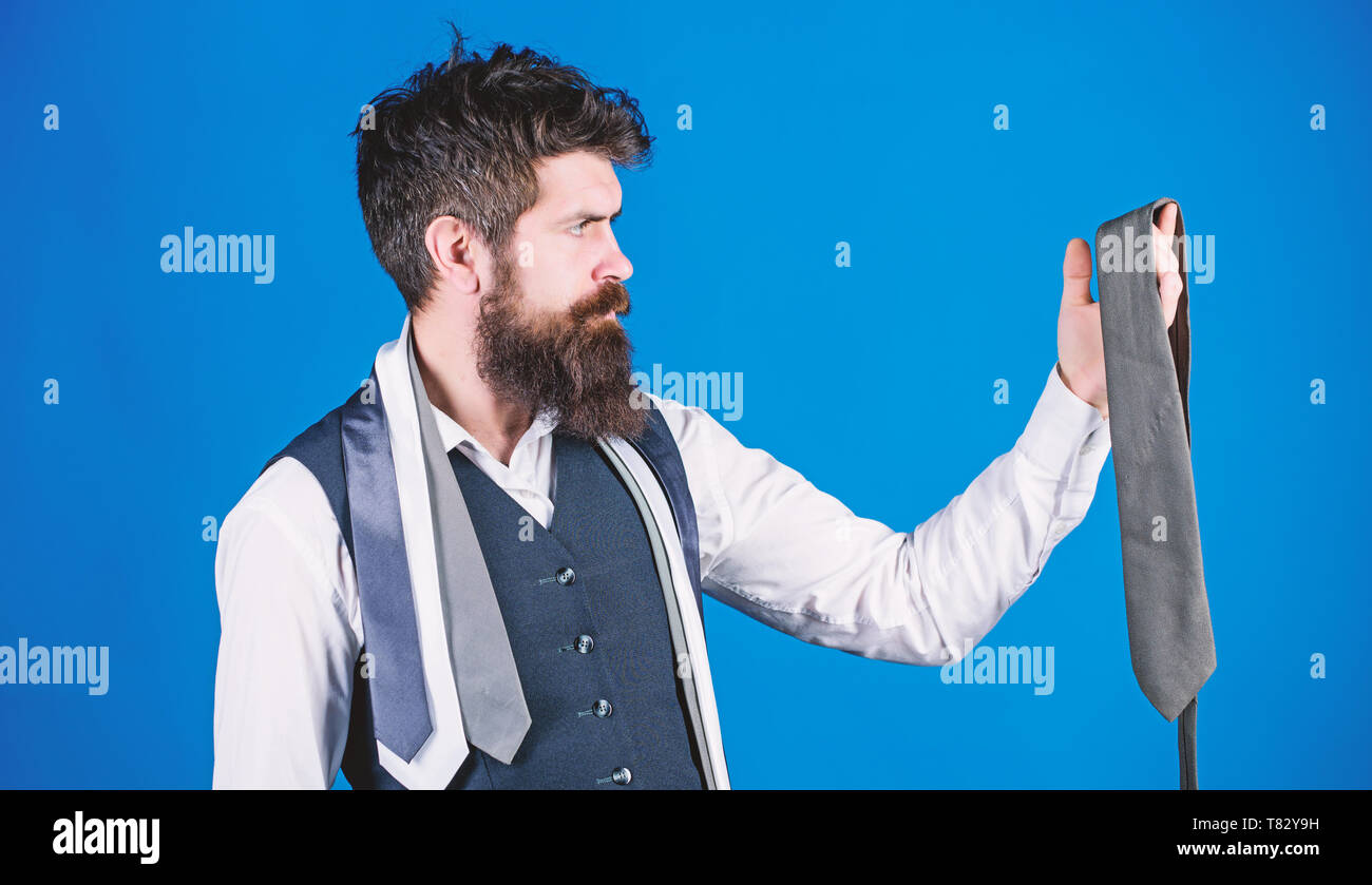Accessory preserving the professional business look. Bearded man choosing menswear accessory. Businessman looking at luxury necktie accessory. Brutal caucasian man holding fashion accessory. - Stock Image
