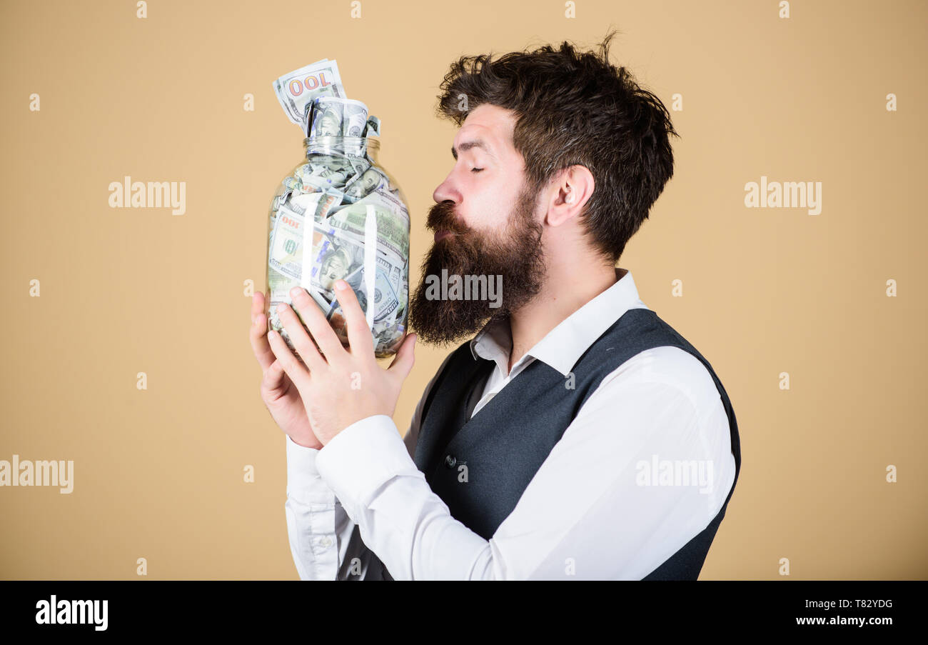 Attractive investment. Bearded man investor kissing glass jar with investment money. Successful businessman making a good investment. His investment producing income. - Stock Image