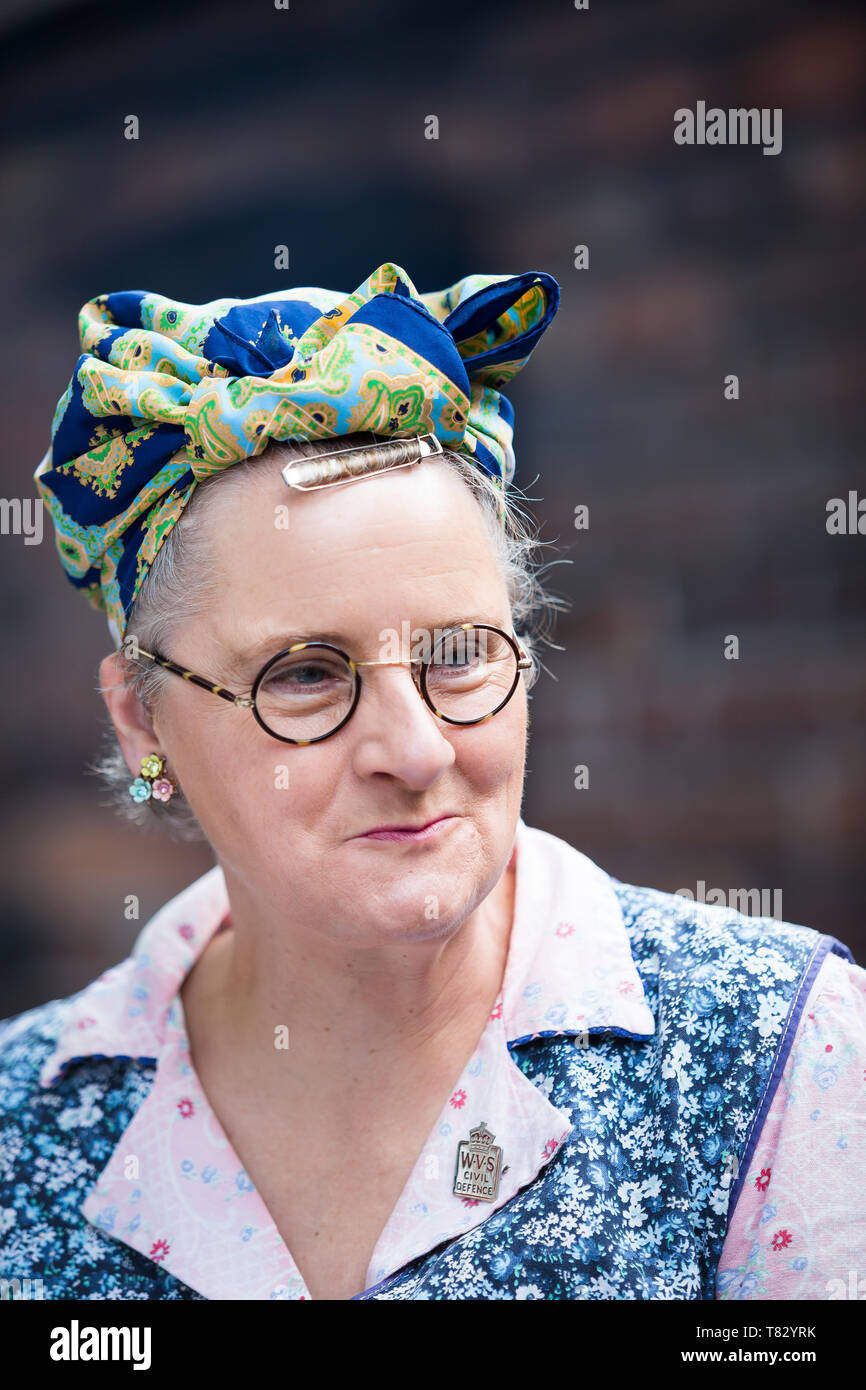 Close-up, front view portrait of 1940's woman in overalls as housewife from WWII, Black Country Living Museum, 1940's wartime weekend, summer 2018. - Stock Image