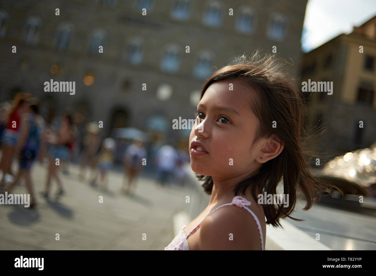 Lifestyle portrait of a preteen Asian girl standing on the sqaure in Siena enjoying the sights and exploring whilst on holiday Stock Photo