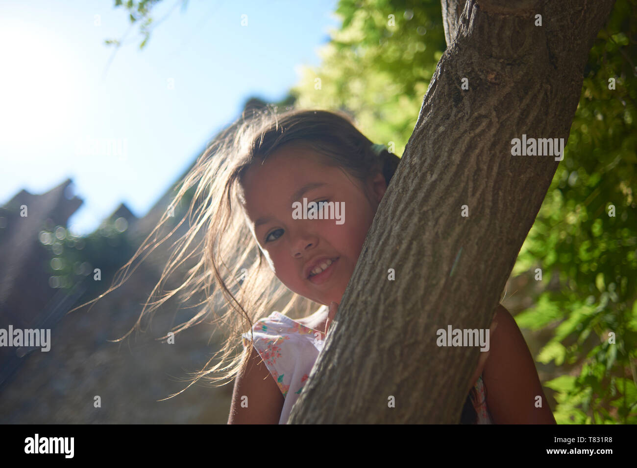 Cute smiling and happy Asian girl posing in bright sunshine in summer in Italy - Stock Image
