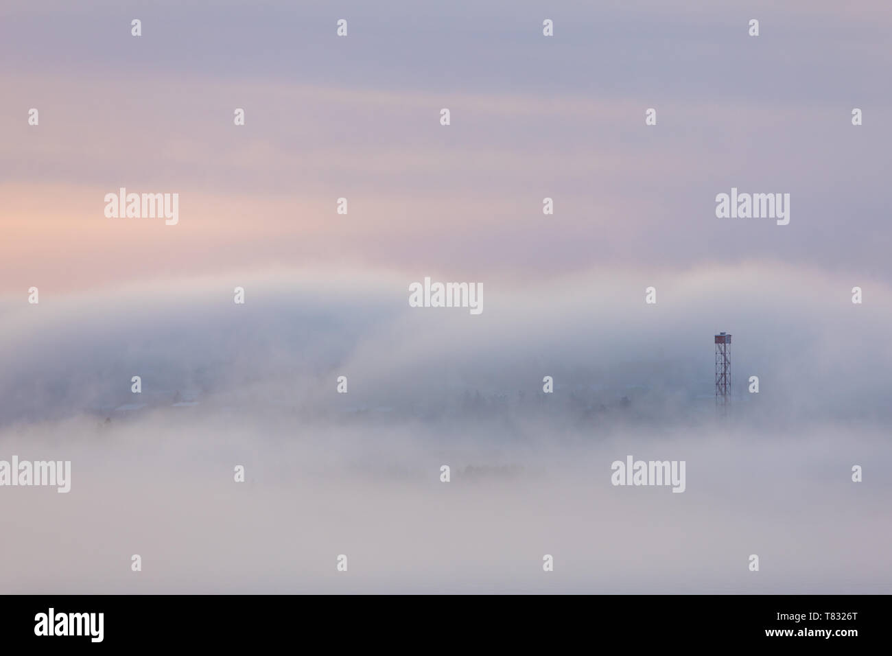 Thick fog at sunrise over hill and city buildings Stock Photo