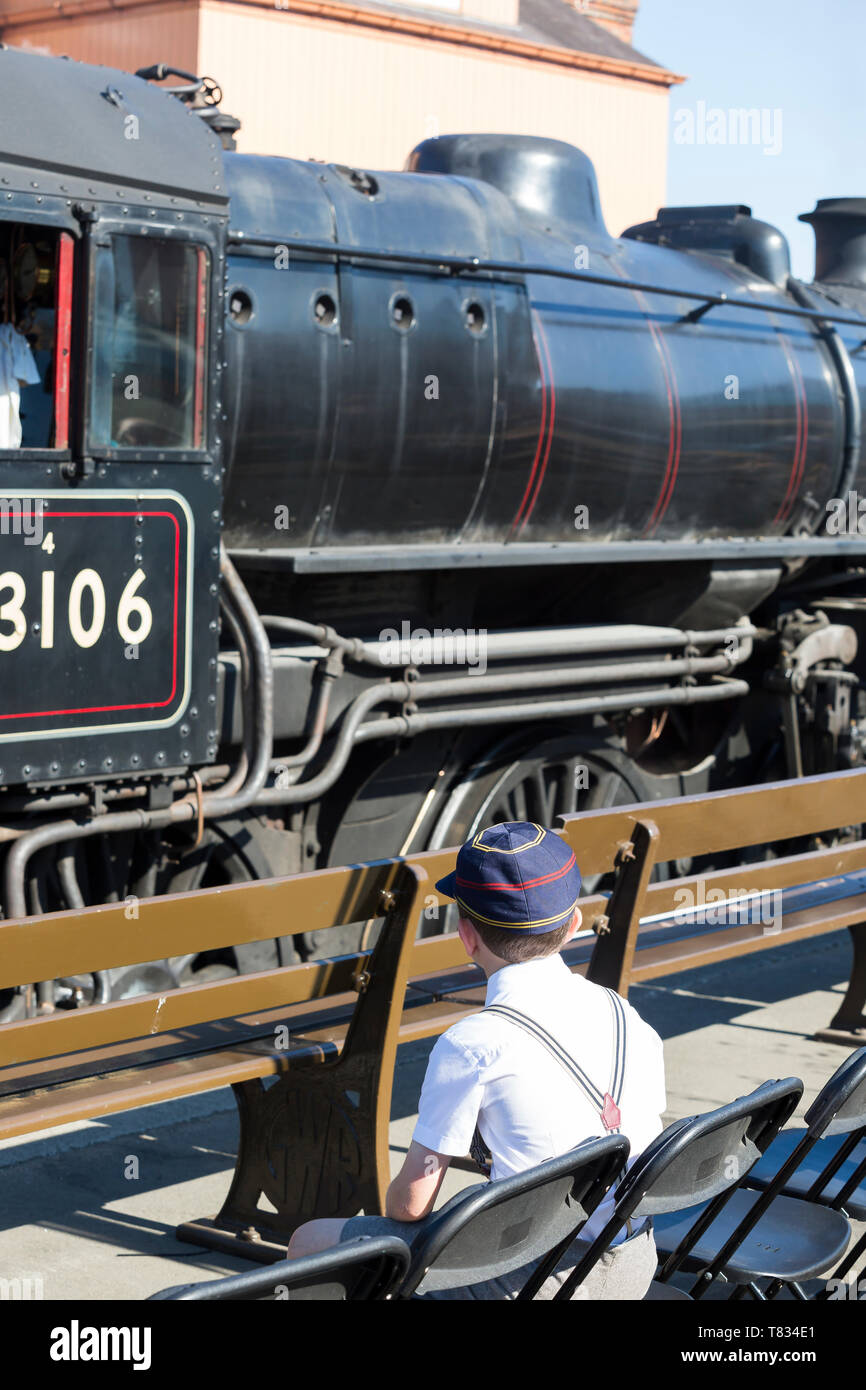 SVR wartime event: rear view of 1940's school boy in cap & braces, sitting on platform watching vintage steam trains dreaming of becoming train driver - Stock Image