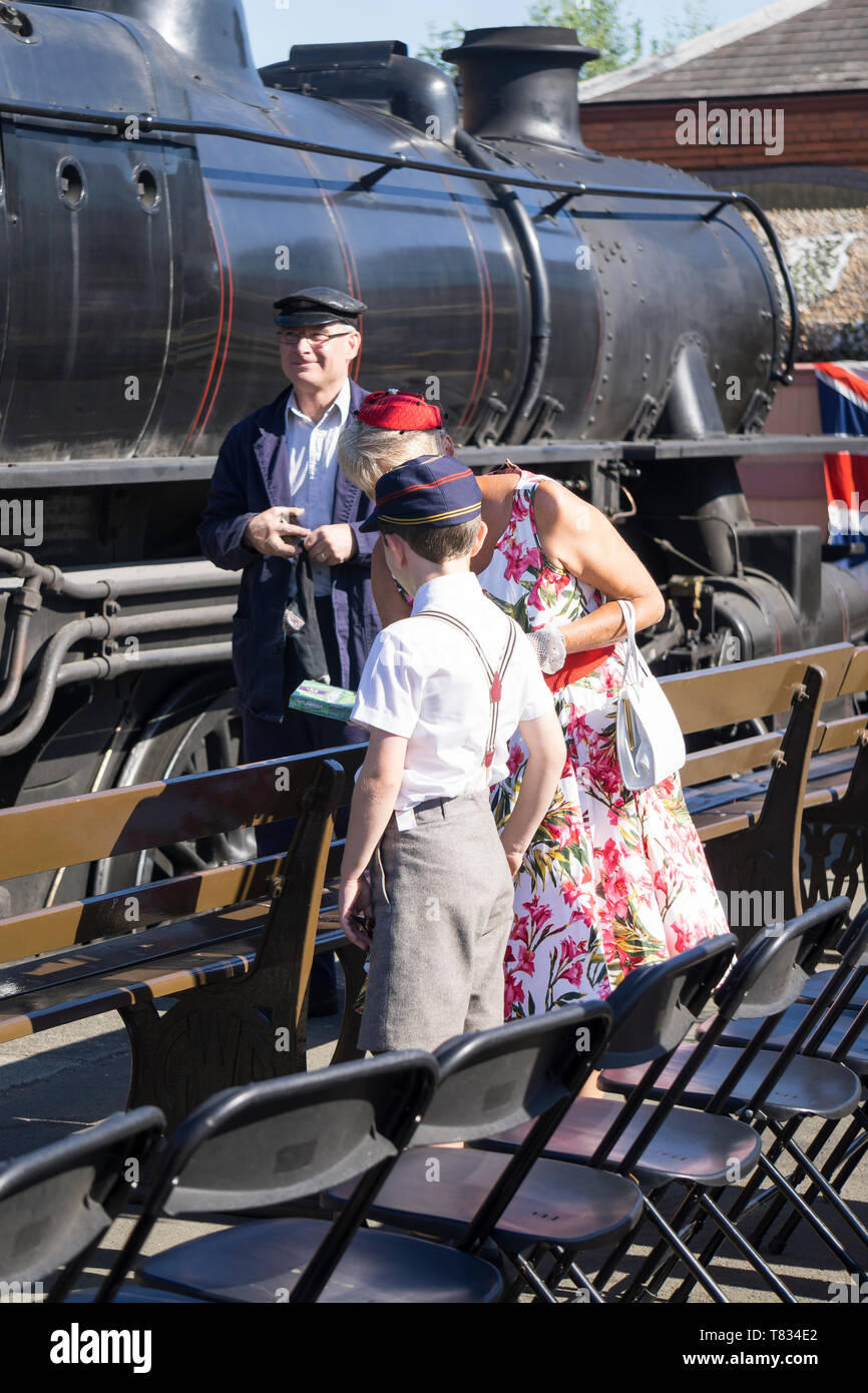 Severn Valley Railway 1940's wartime event: kind lady in 1940s dress offering chocolates to vintage boy in school uniform on platform by steam train. - Stock Image