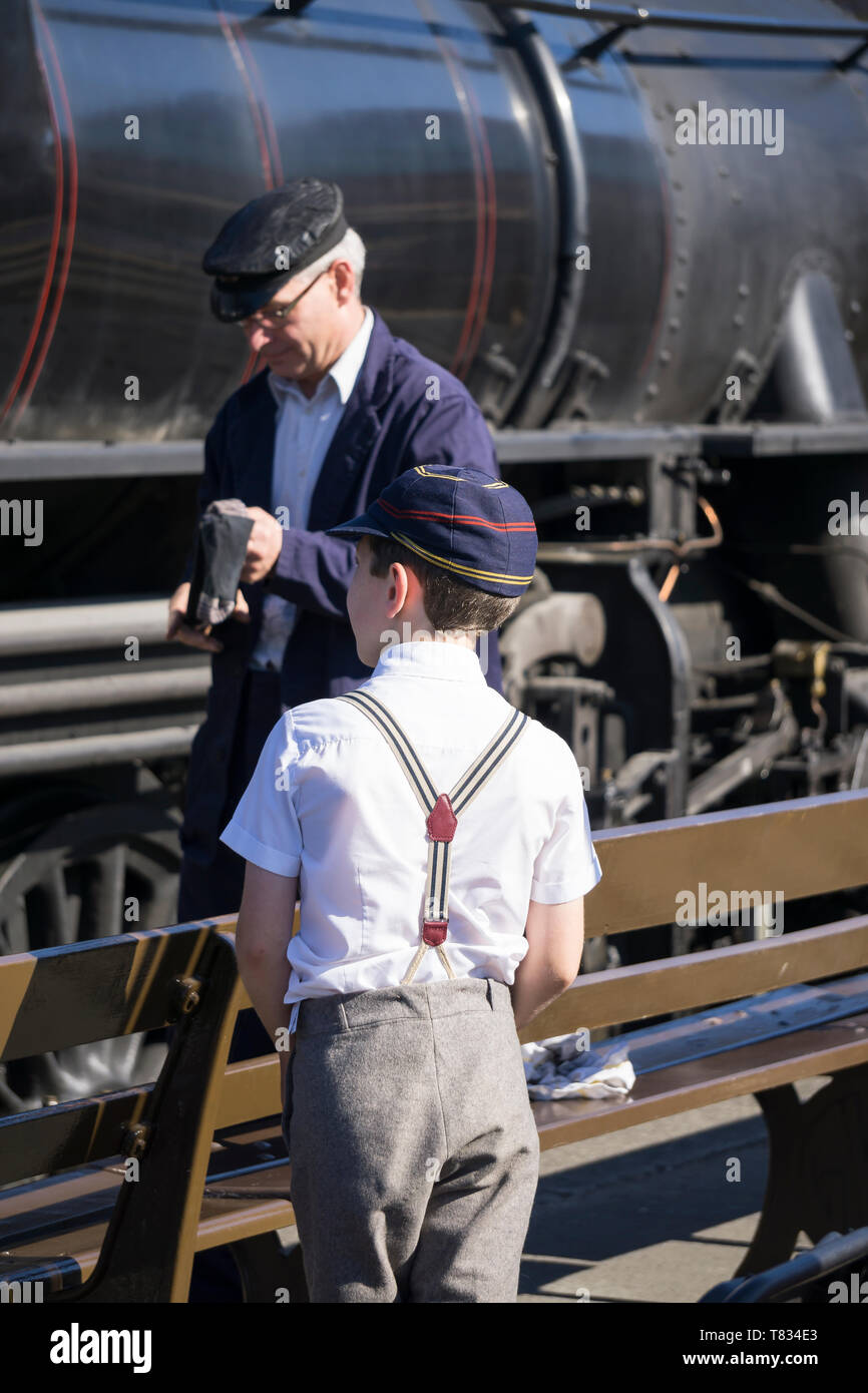 Severn Valley Railway, 1940's wartime event, 2018. Close-up rear view of  school boy in vintage school cap & braces watching steam trains on platform. - Stock Image