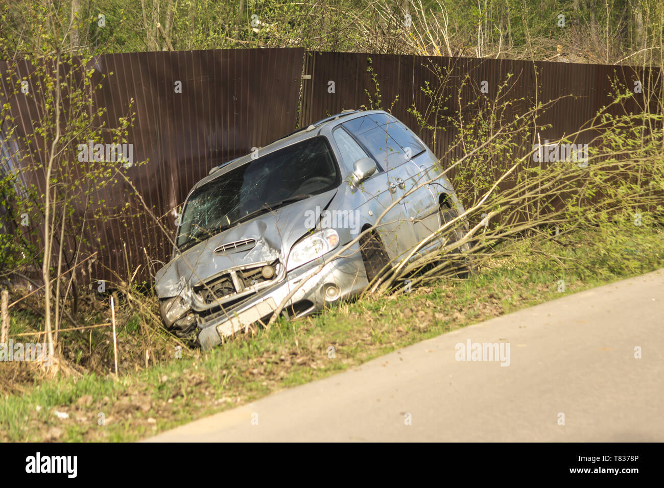 Car accident on a country road. The car is broken in front, slid into a ditch and damaged a metal fence. - Stock Image