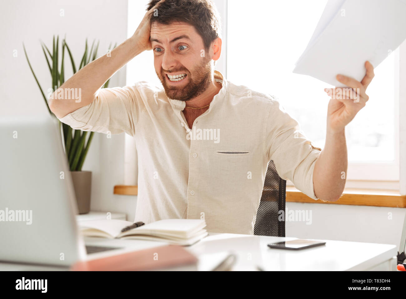 Image of stressful office worker 30s wearing white shirt using laptop and paper documents in modern workplace - Stock Image