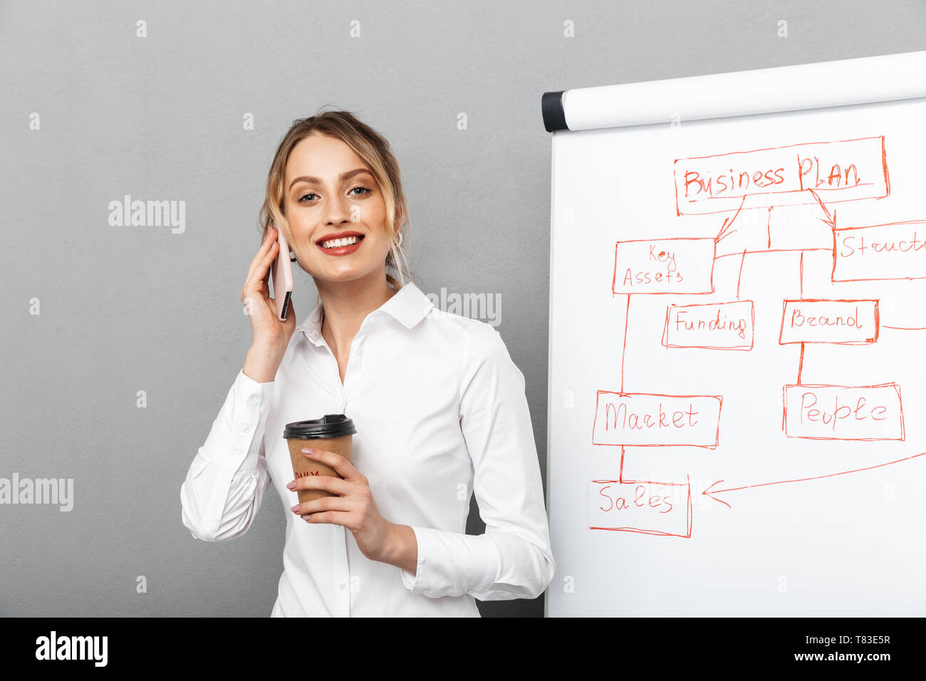 Image of lovely businesswoman in formal wear drinking coffee while making presentation using flipchart in the office isolated over gray background - Stock Image