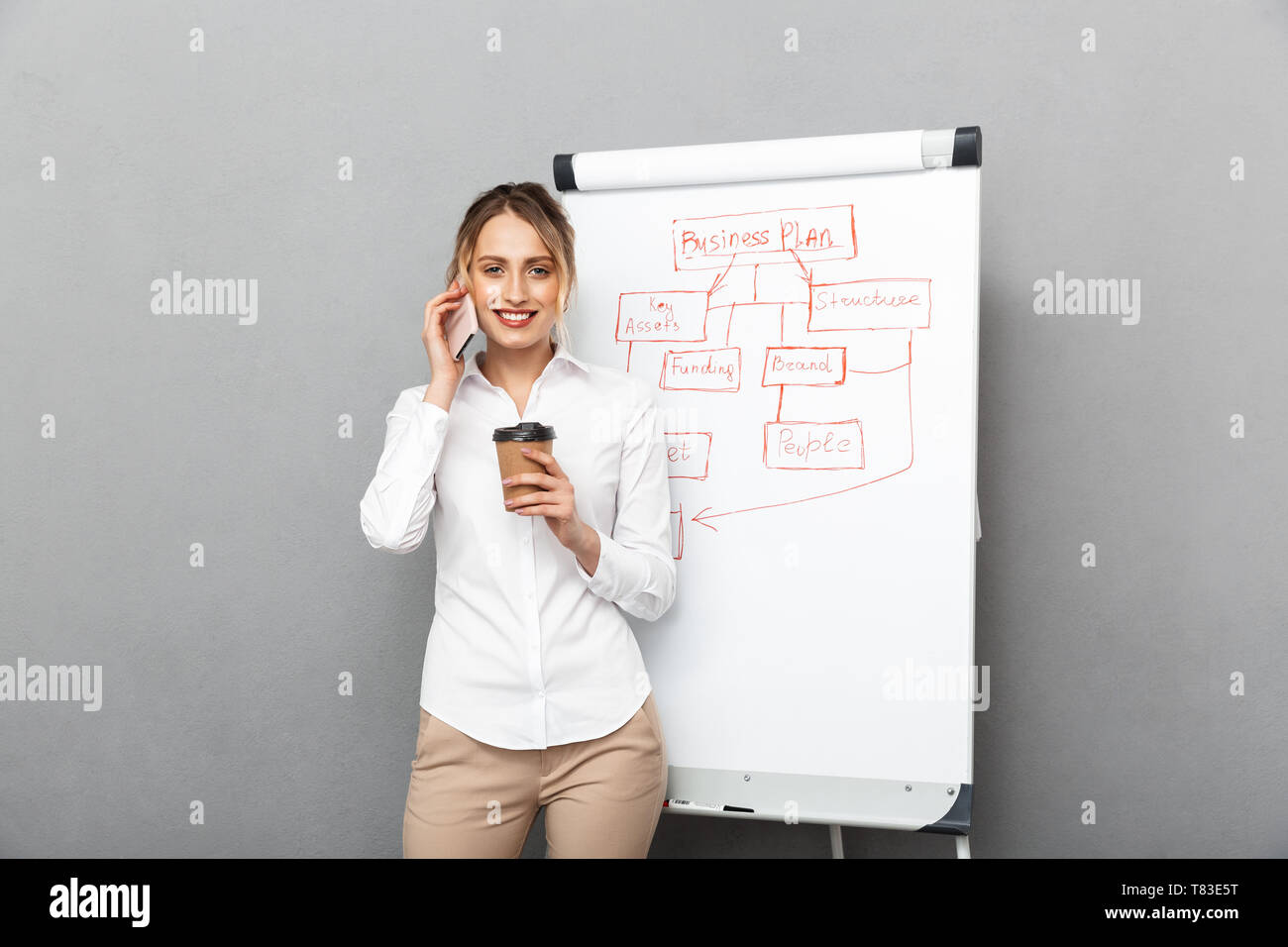 Image of satisfied businesswoman in formal wear drinking coffee while making presentation using flipchart in the office isolated over gray background - Stock Image