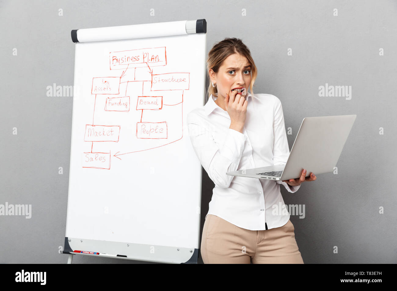 Image of young businesswoman in formal wear using flipchart and laptop while making presentation in the office isolated over gray background - Stock Image