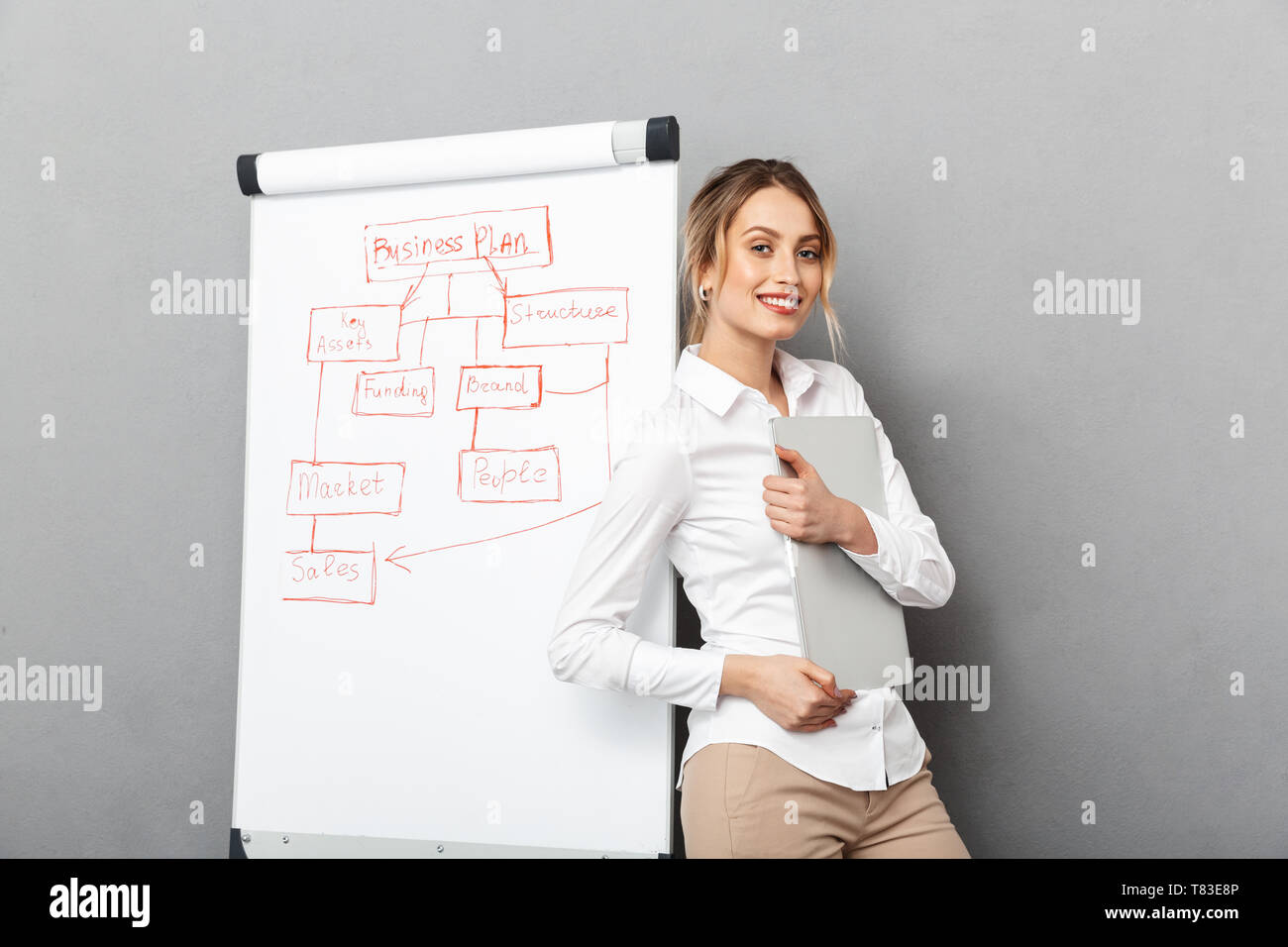 Image of cheerful businesswoman in formal wear using flipchart and laptop while making presentation in the office isolated over gray background - Stock Image