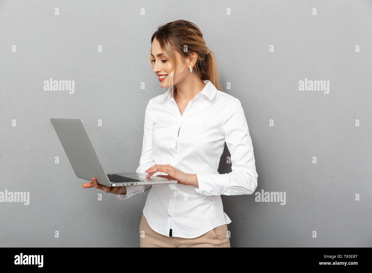 Photo of businesslike woman in formal wear standing and holding laptop in the office isolated over gray background - Stock Image