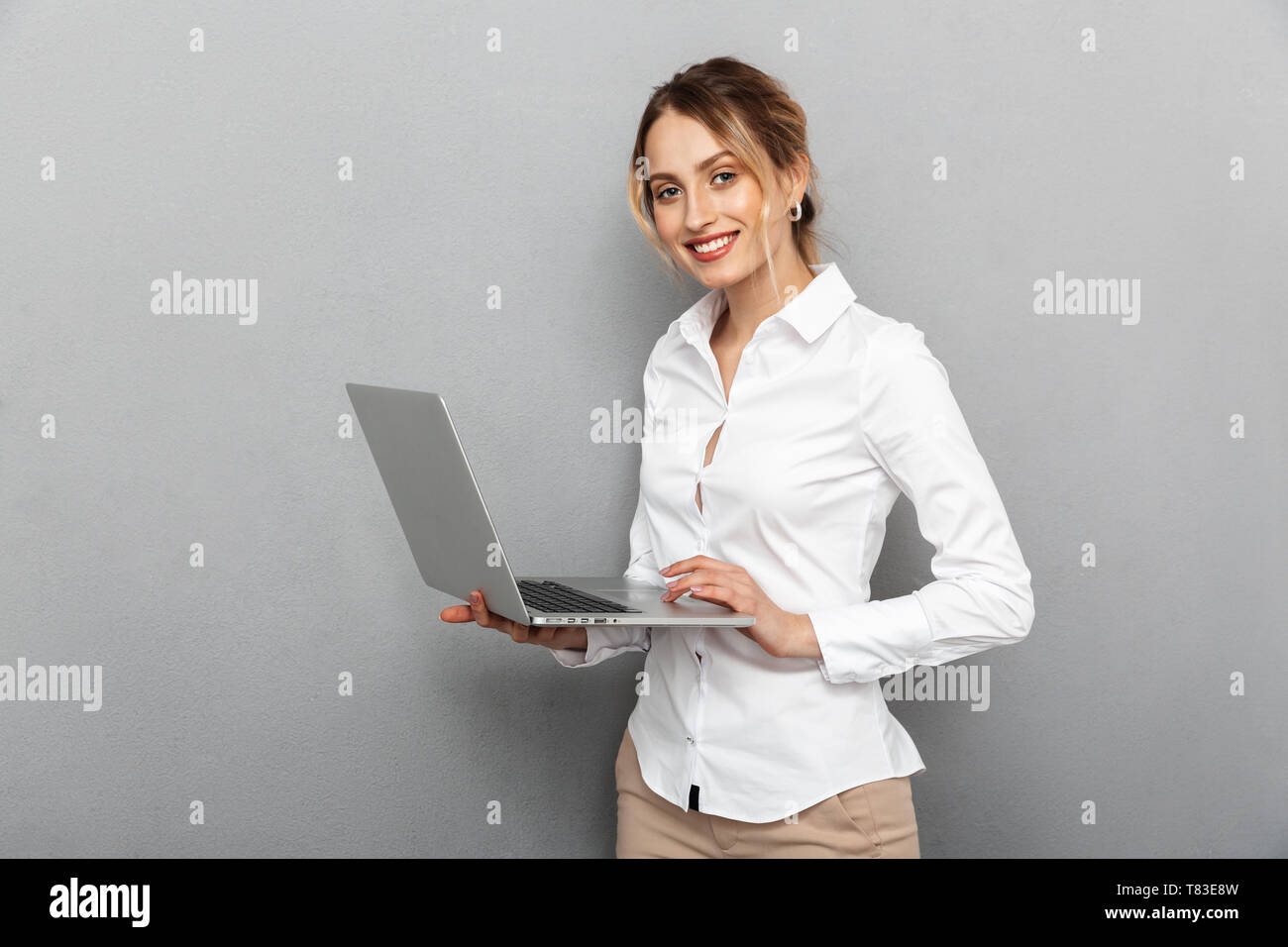 Photo of smart woman in formal wear standing and holding laptop in the office isolated over gray background Stock Photo