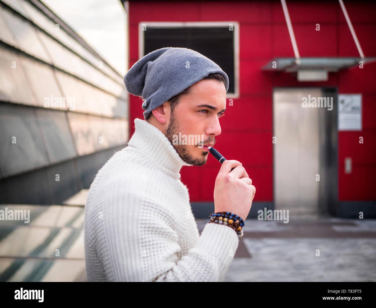 Young man vaping, smoking e-cigarette outdoor - Stock Image