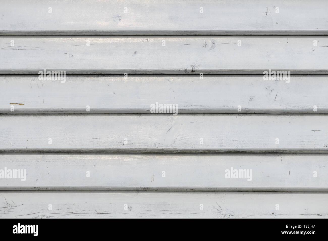 White vintage wooden boards in overlap cladding pattern, front view as copy space or graphic design background - Stock Image