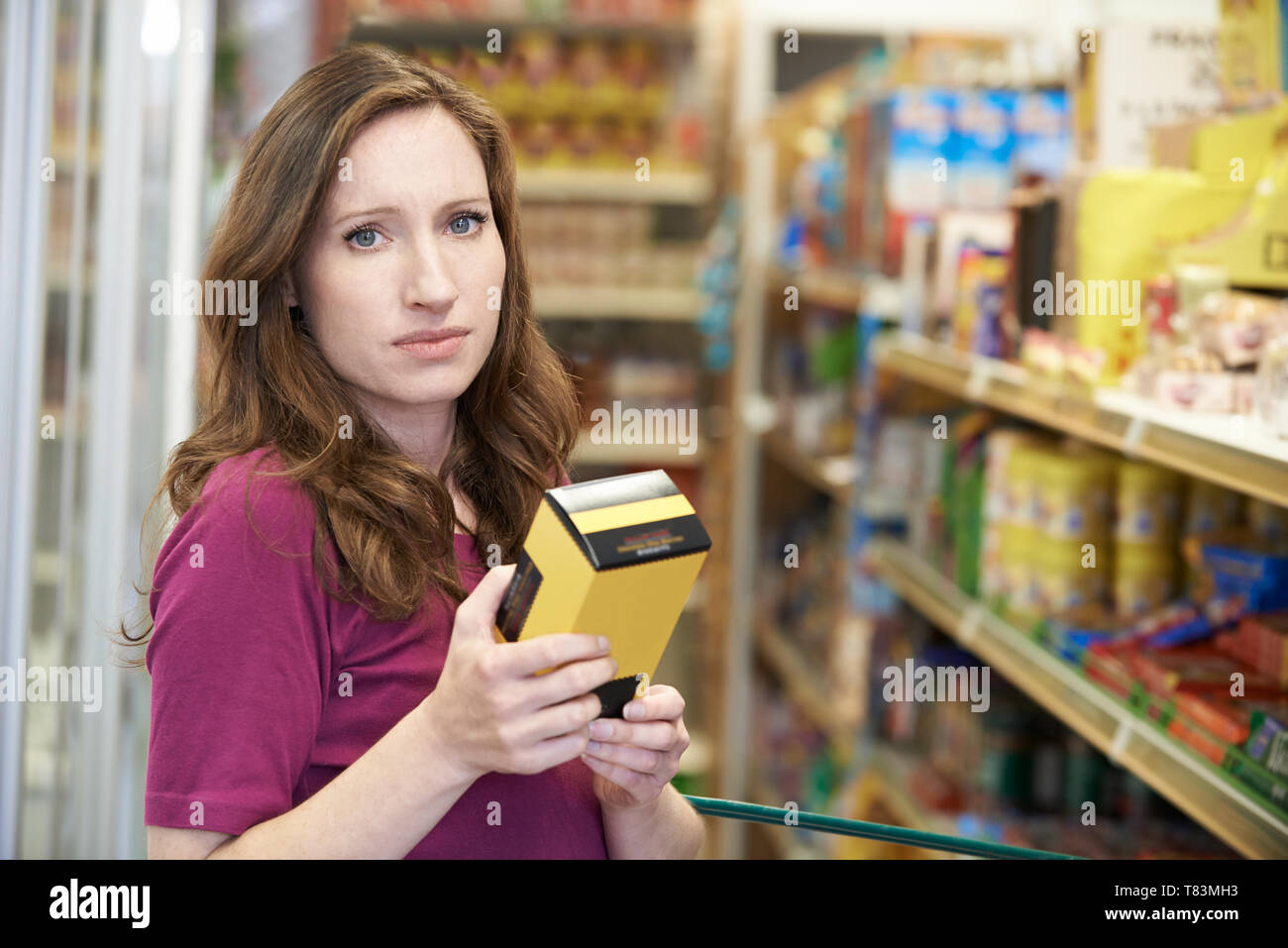 Portrait Of Woman Checking Food Labelling On Box In Supermarket - Stock Image