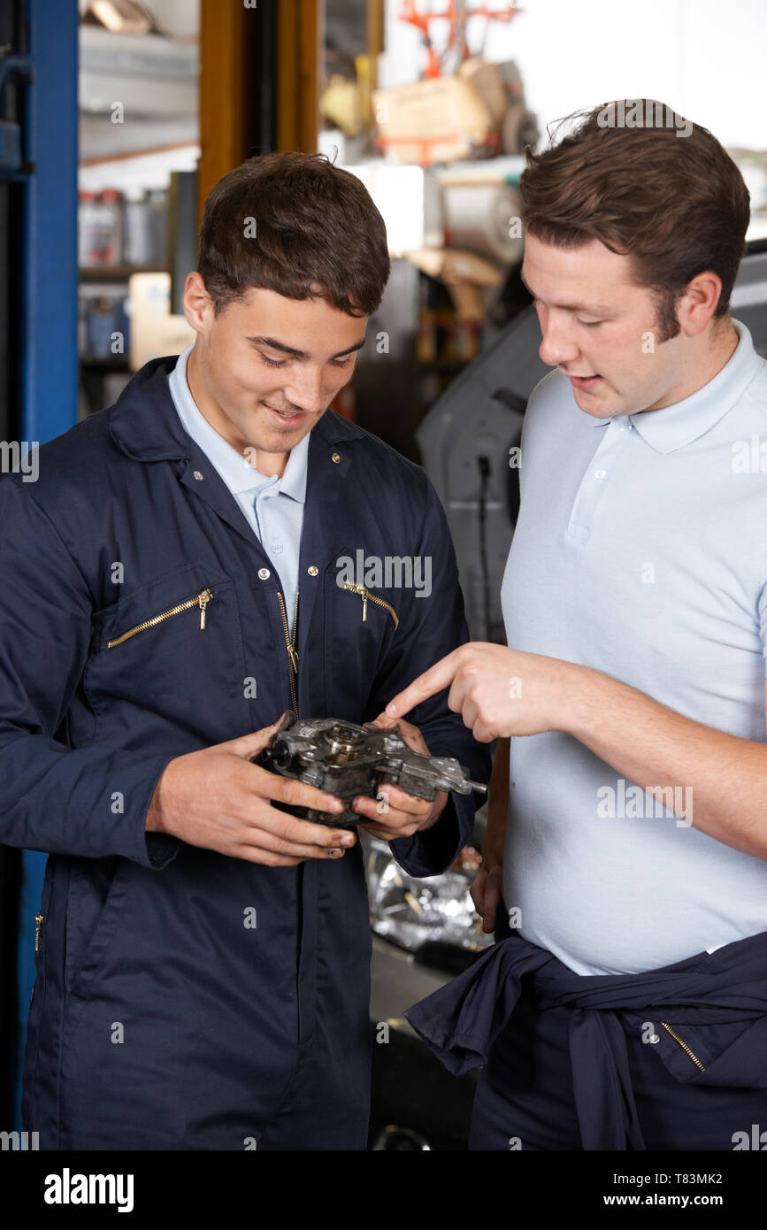 Mechanic In Garage Helping Apprentice To Fix Car Engine - Stock Image