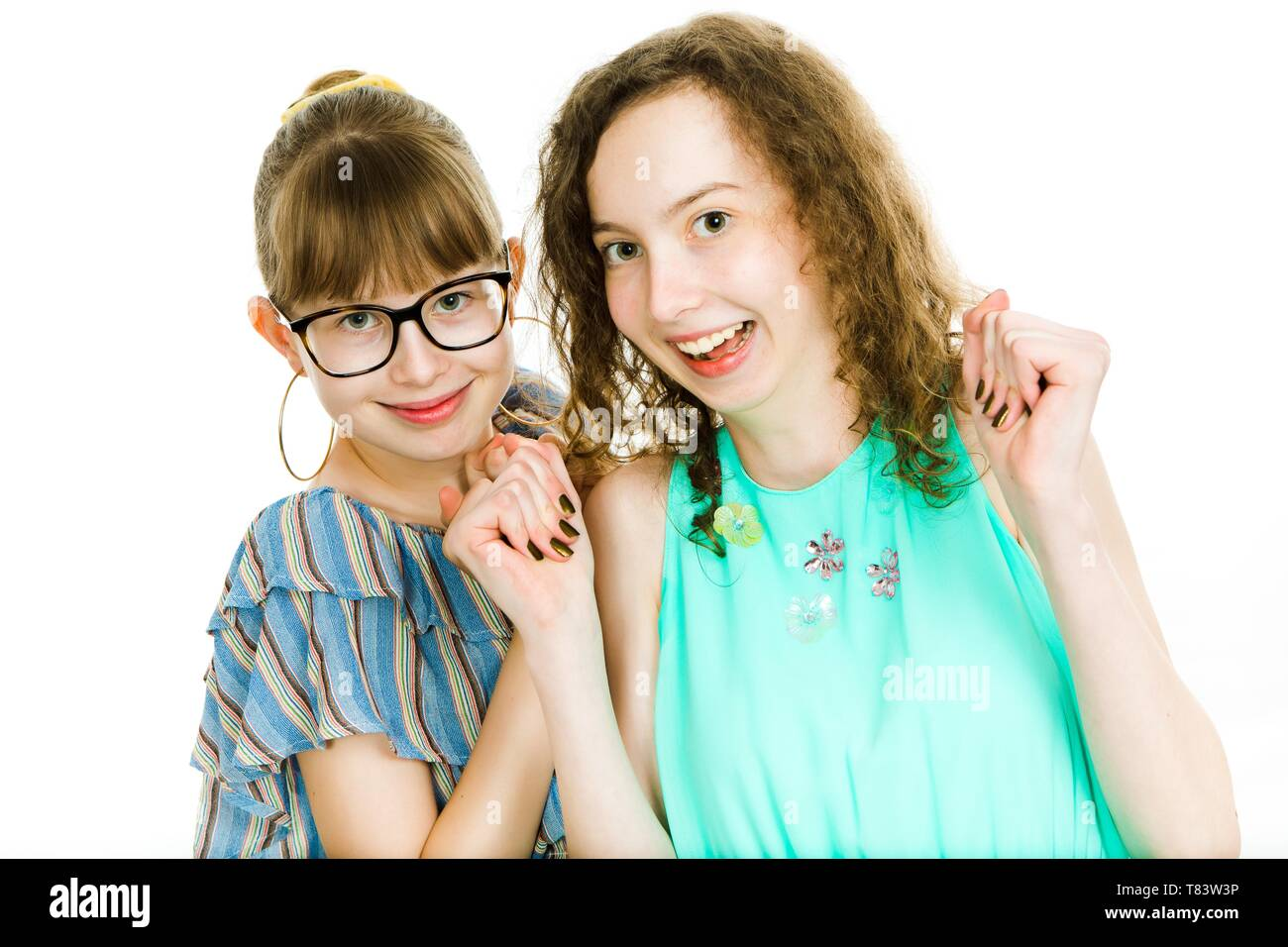 Two teenaged sisters posing together - shows happiness are smiling - white background Stock Photo