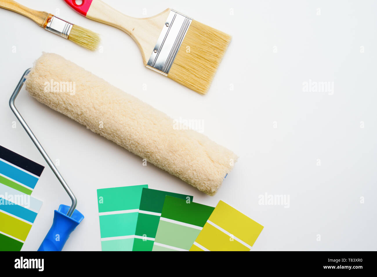 Photo of palette with blue and green colors, roller, brushes - Stock Image