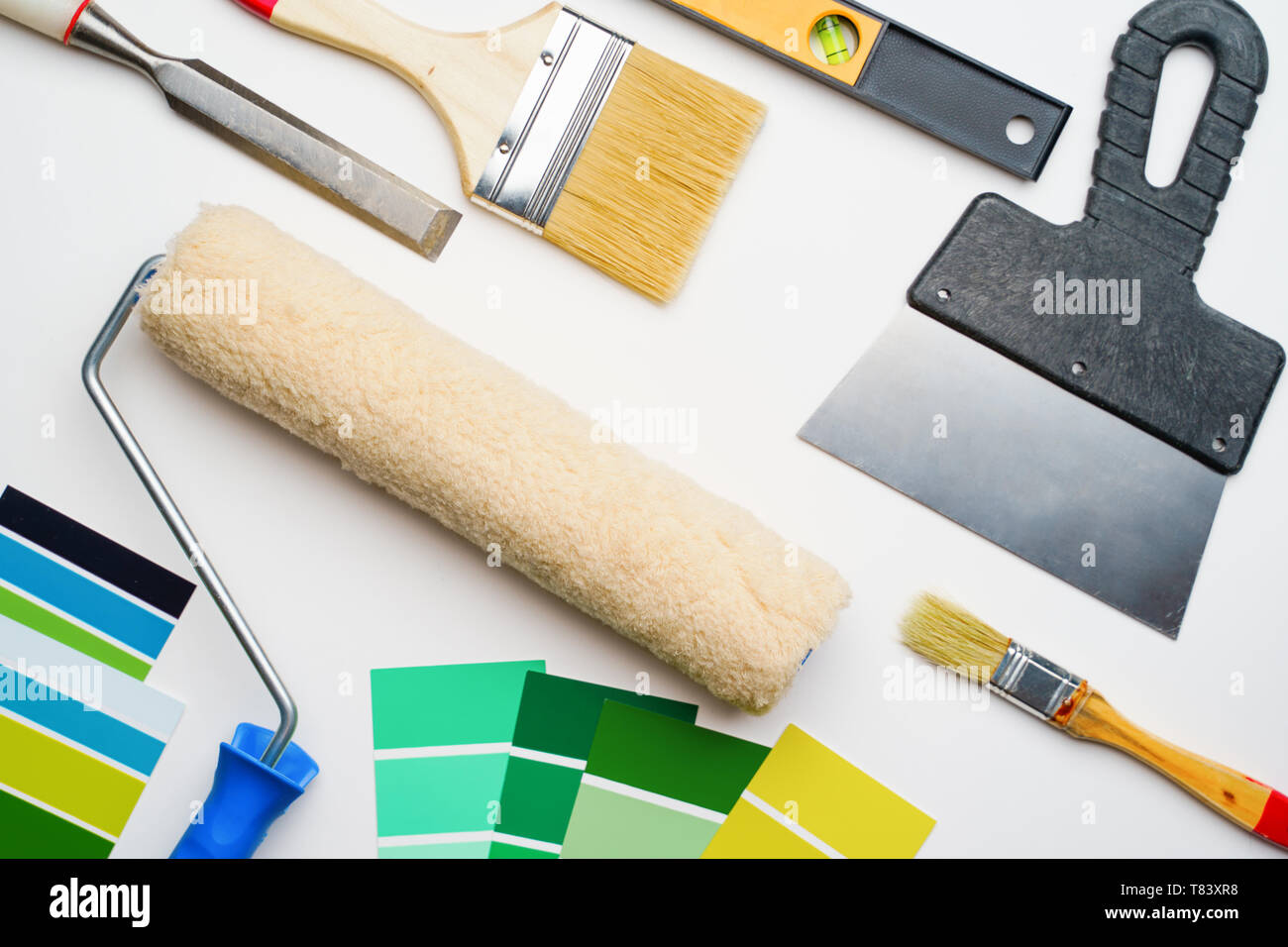 Photo of palette with blue and green colors, roller, brushes, trowel - Stock Image