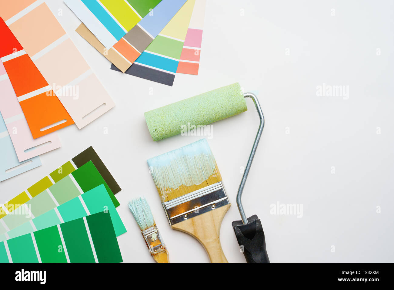 Image of palette with blue and green colors, roller, brushes - Stock Image