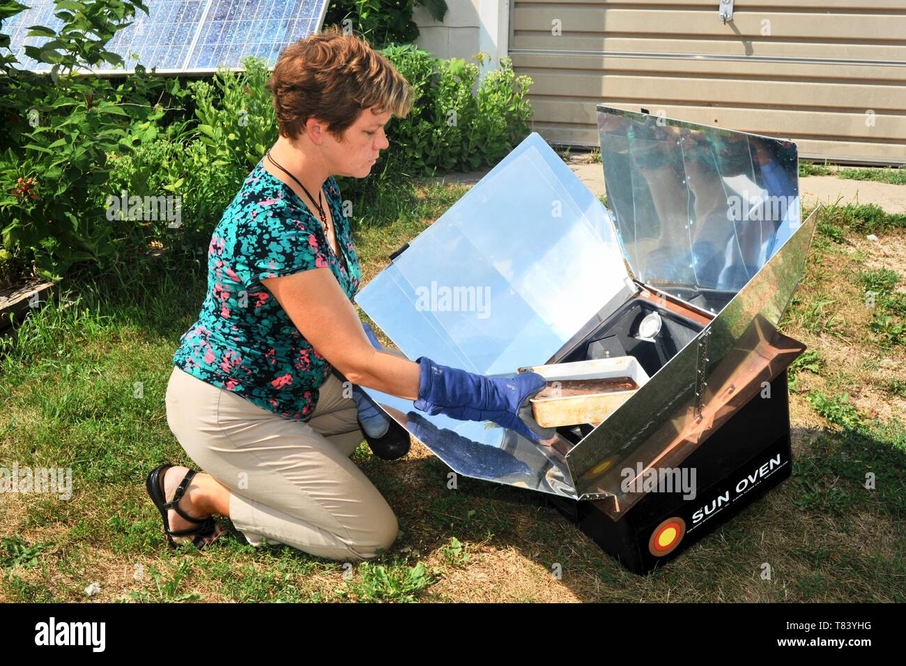 Woman baking fresh bread with farm-raised ingredients in a Sun Oven, cooking food with the heat from the sunlight, in Wisconsin, USA Stock Photo
