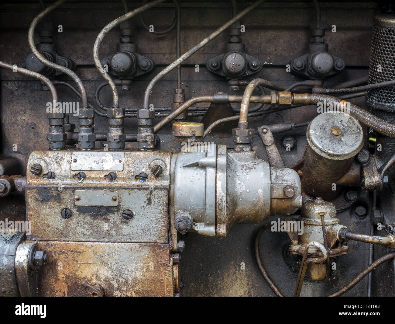 A close-up of a section of a vintage tractor engine on an old farm, Lake District, Cumbria, UK - Stock Image