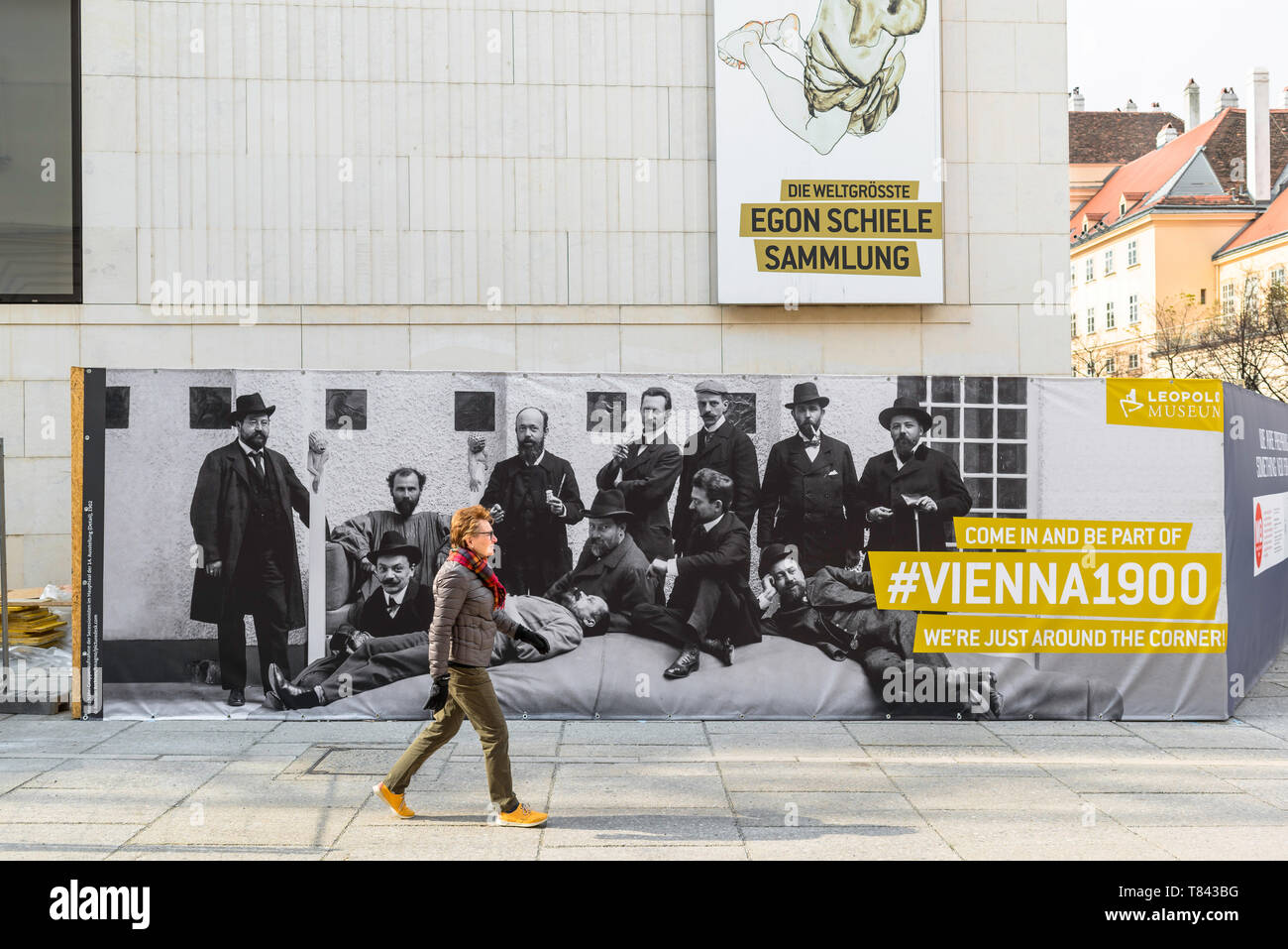 Vienna Secession, view of a middle aged woman walking past a Leopold Museum advertisement celebrating artists of the Secession movement in Vienna. Stock Photo