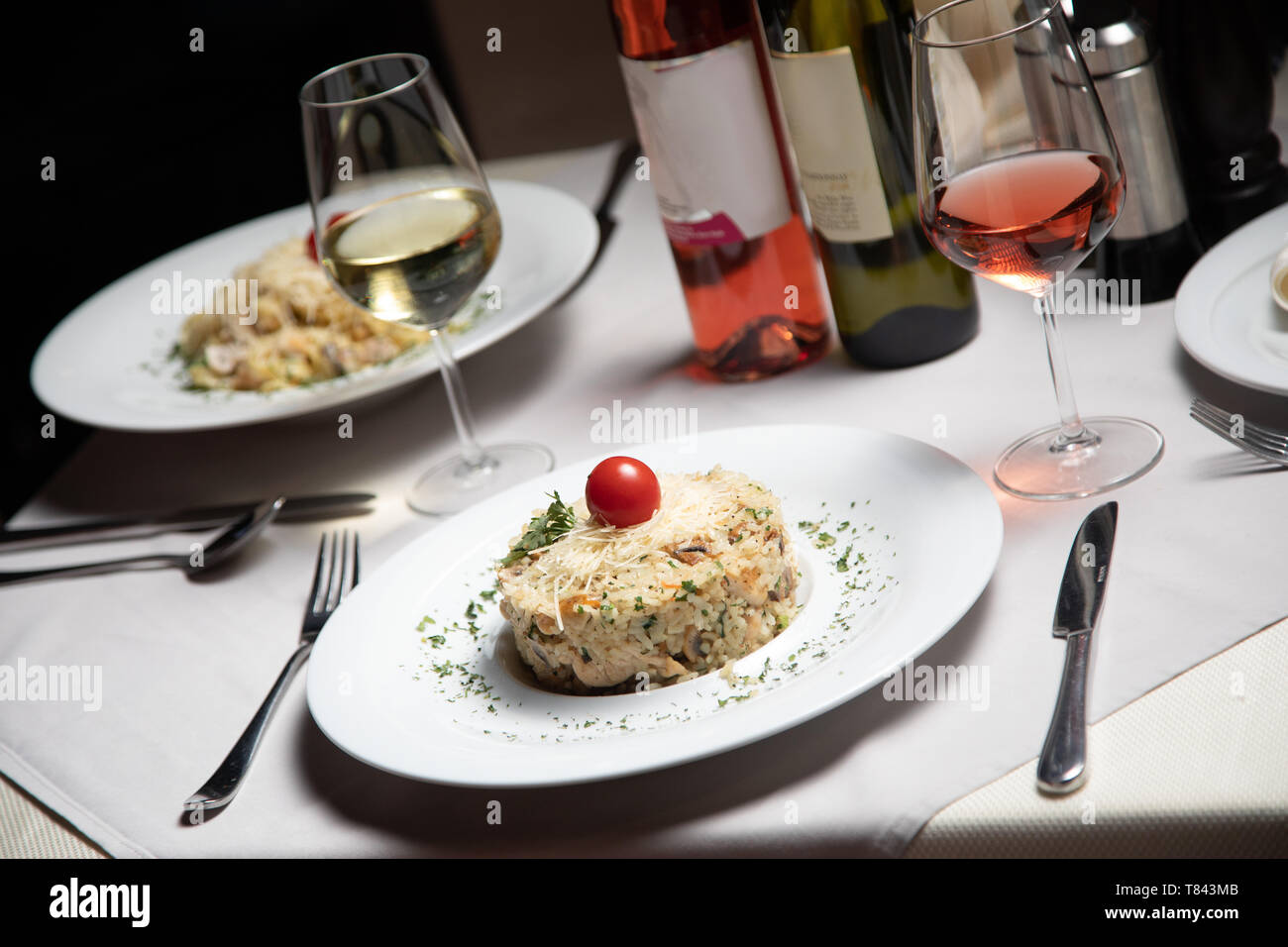 Risotto with white wine glass served at restaurant table - Stock Image