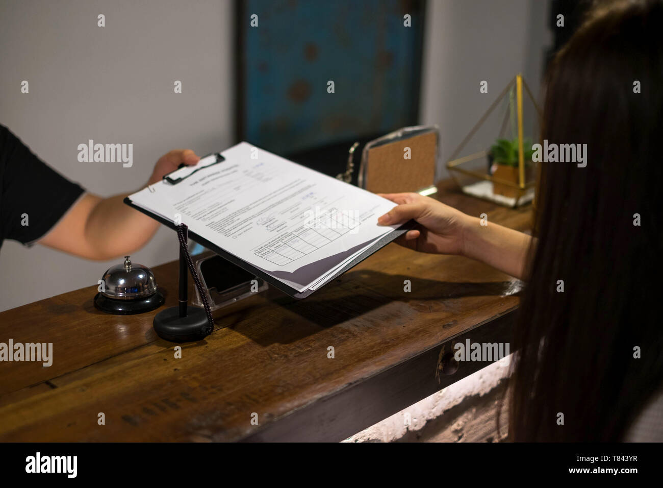 Receptionist's sent the documents to guest for signing and filling up form check-in process.Hotel concept. - Stock Image