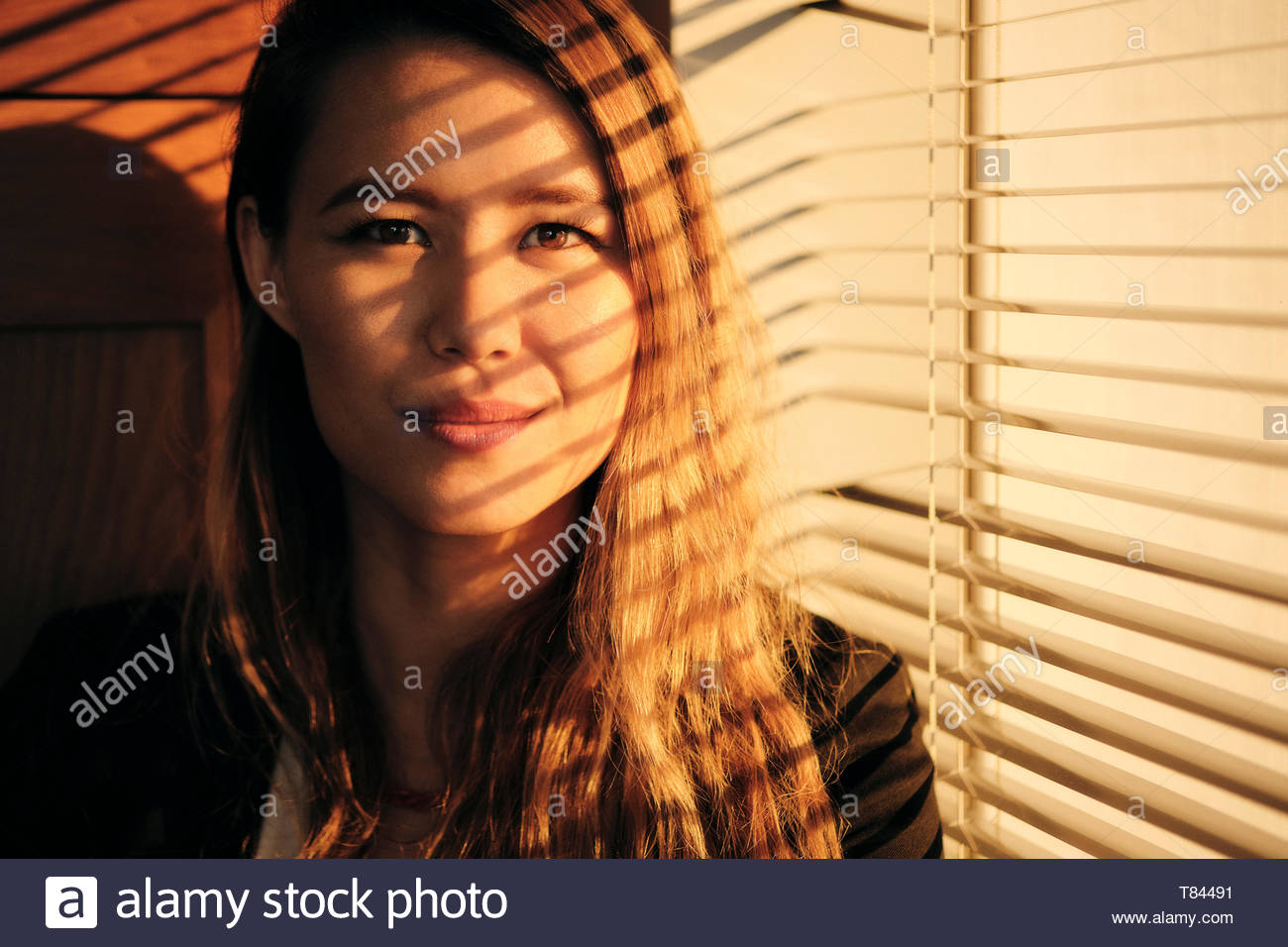 Young woman by window at sunset Stock Photo