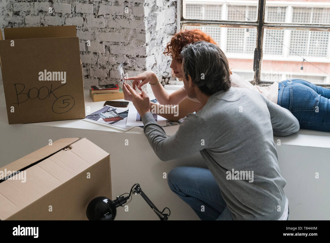 Couple moving into industrial style apartment, on window ledge looking at photo - Stock Image