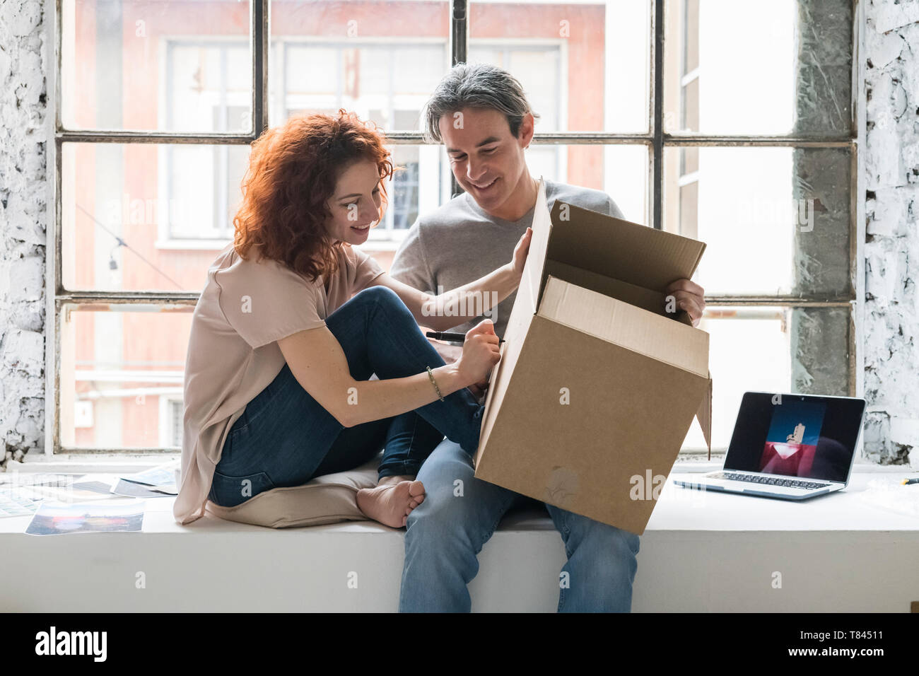 Couple moving into industrial style apartment, sitting on window ledge writing on cardboard box - Stock Image
