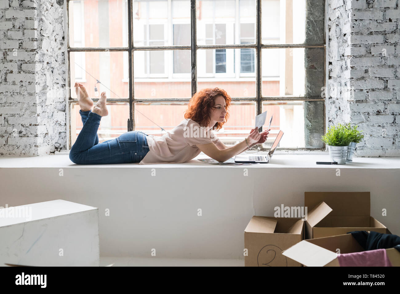 Mid adult woman moving into industrial style apartment, lying on window ledge looking at photograph - Stock Image